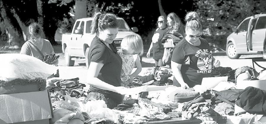 Ashley Vollers and her daughter Aspen of St. Paul were among the many people checking out the tables filled with items at the Westside Covenant Church during the two-day citywide garage sale. News-Register/Kurt Johnson