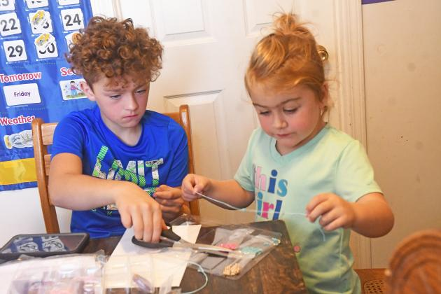 Keagen and Emmah White work on a bracelet making kit together. In front of them is a seed tray that Emmah has started working on.