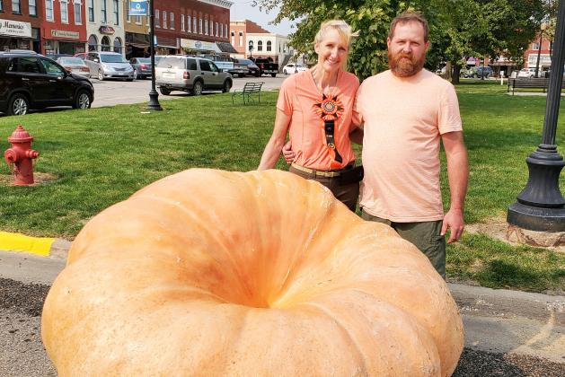 Beth Wood (left) and her boyfriend Traver DeMaranville pose with the second-place, 1,365 pound pumpkin at a competition in Bloomfield, Iowa.