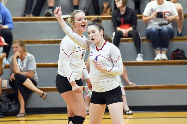 Alexis Kalkwarf (4) and Brianna Wilshusen celebrate a point during HPC's five-set victory over McCool Junction.