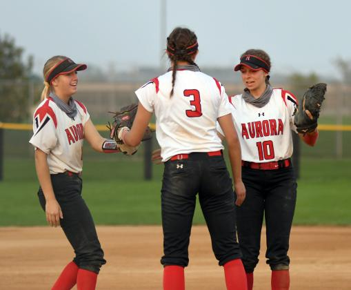 Kylie Larson (left) and Brooklyn Moody (right) send words of encouragement to Aurora pitcher Rylee Olsen during subdistrict play Monday.