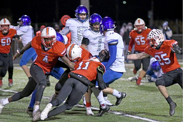 The Husky defense of Mack Owens (4) Brady Collingham (11) and Jameson Herzberg (25) converge on the hit during Aurora's 21-12 win over Plattsmouth.