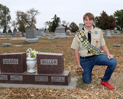 Astin Kennedy kneels next to one of the many markers that he placed in the Aurora Cemetery as part of his Eagle Scout project.