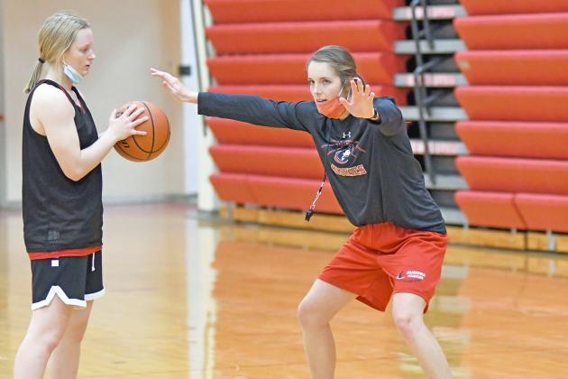 Kelly Boshart, Aurora's new girls basketball coach demonstrates during a drill in preseason workouts ahead of Thursday's season-opener.