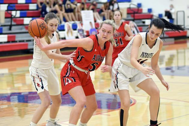 Aurora's Jaylee Schuster flips the ball behind her in heavy traffic during the Lady Huskies' 56-38 loss to Adams Central Thursday night.