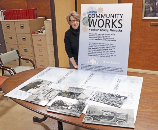 Tina Larson, executive director of the Plainsman Museum, stands proudly with some of the panels that will be on display for their Community Works exhibition.
