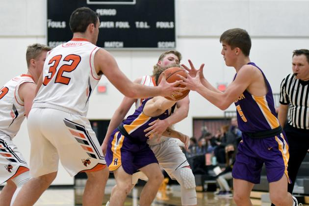 A fight for the ball ensues with Giltner's Jacob Smith (32) and Hampton's Drake Schafer (5) with others in pursuit.