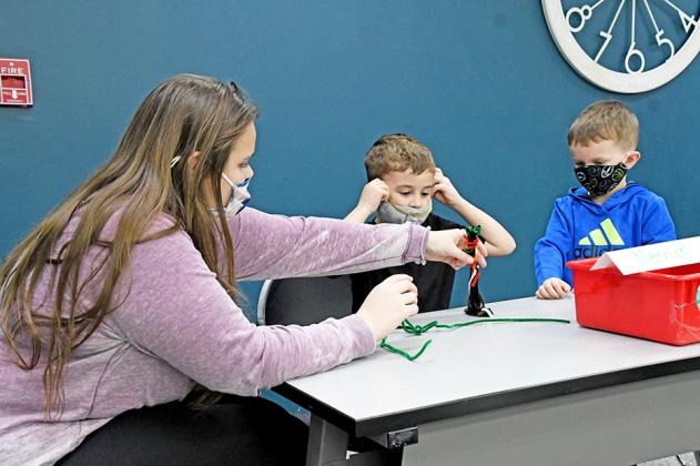 Journey Noyes (left) helps students in the after-school club work on a science experiment. She along with Sydney Dyer assist with camps, clubs and daily activities.
