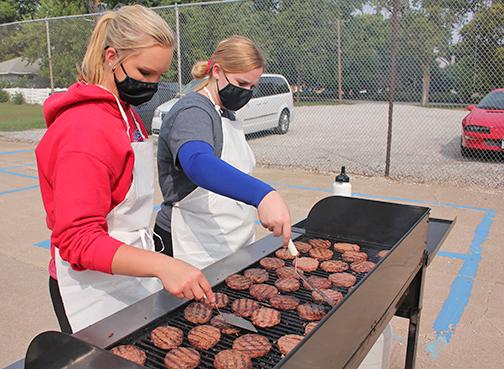 Brianna Wilshusen (left) and Aubree Quast work together to grill up hamburgers for HPC students.
