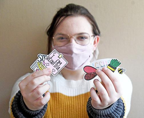 Carli Hauf holds some of her current designs available through Happy Life Stickers, a recent hobby that she has taken to Etsy and Facebook.