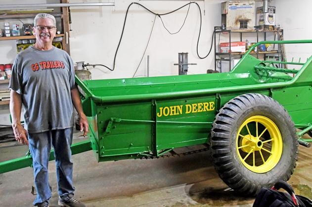 Gary Andrews stands with his current project, a John Deere wooden manure spreader.