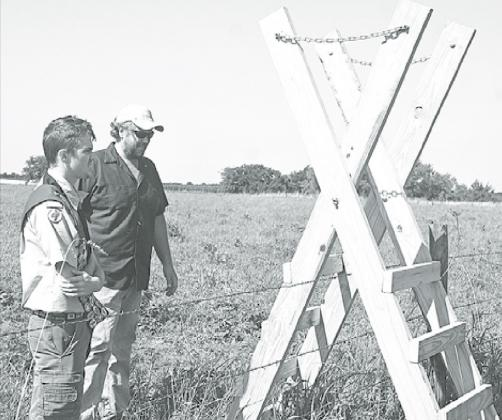 Colin Kennedy (left) looks over his project with Jeff Gustafson after it was set up in Gjerloff Prairie. News-Register/Jeni Moellenberndt