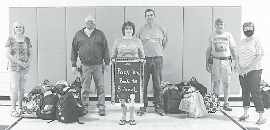 Marilyn Vrana (left), David Olson, Holly Schmit, Phil Troester, Bob Spotanski and Laura Jobman stand with a portion of the 93 donated backpacks for students at Aurora Elementary and Middle School. News-Register/Jeni Moellenberndt