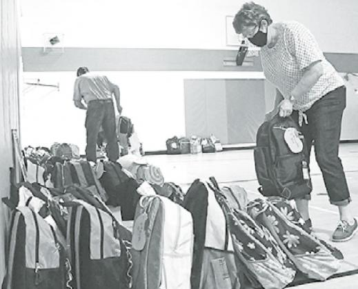 Laura Jobman works to sort out the incoming backpacks by grade and gender. News-Register/Jeni Moellenberndt