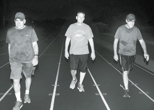 Pictured from left, Kelly Grossnicklaus, Jeff Bart and Todd Jensen walk on the AHS track Friday, the 20th anniversary of when the daily 3-mile routine began. News-Register/Kurt Johnson