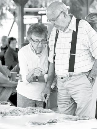 Ernie and Leota Snell of Sutton scan over the many pie selections at Saturday's Stockham celebration. News-Register/Kurt Johnson